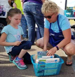 As part of Summer Read 6, United Way board member Ruth Uecker helps a student pick out a free book. Summer Read 6 is one of 34 local nonprofit programs supported by United Way grants this year.