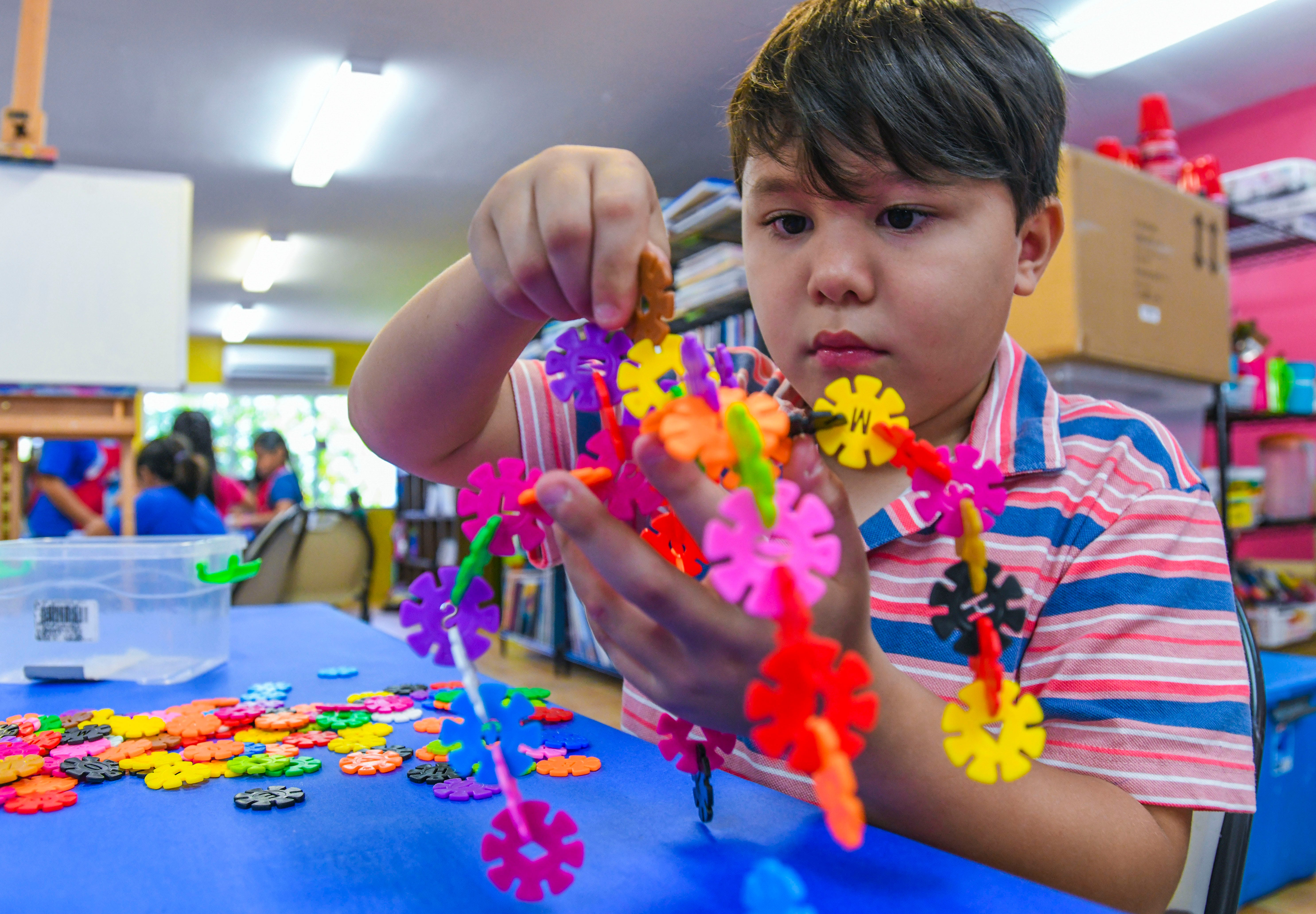 Russell Strohmeyer connects discs together as he engages in the STEM activity to create his concept of a walking robot during an art session at the Color Guam art studio in Hagåtña in this June 14, 2019, file photo.