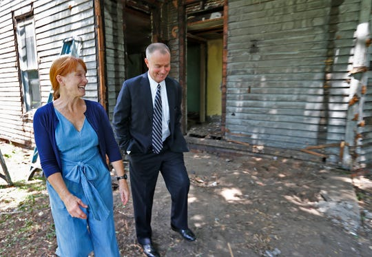 Demolition is underway at 1230 S. Talbott St., Friday, June 14, 2019. The home was used as a backdrop for mayoral candidate Jim Merritt the day before, to launch his housing plan while chastising his Democratic opponent Mayor Joe Hogsett's blighted housing plan.  Karen E Laine, left, walking with Mayor Joe Hogsett after a press conference at the home, and Mina Starsiak Hawk, mother and daughter team of Two Chicks and a Hammer own the property.  Friday, Mayor Hogsett and the renovating homeowners held a press conference to talk about the home's timeline.