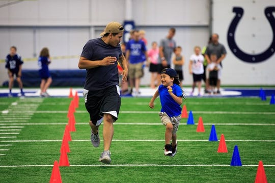 A father races his child during the All-Pro Dad event.