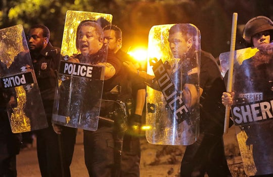 Memphis police brace against the crowd as protesters take to the streets of the Frayser community in anger against the shooting a youth by U.S. Marshals earlier in the evening, Wednesday, June 12, 2019, in Memphis, Tenn.