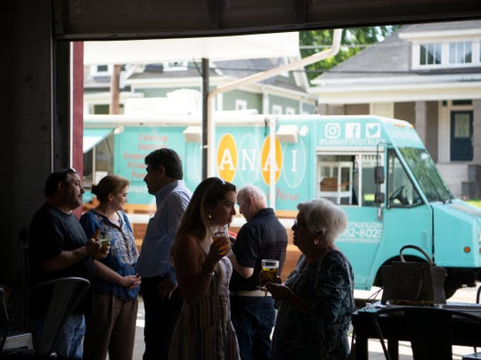 Customers gather at Southside Garage food truck park on their open day, Thursday, June 13, 2019