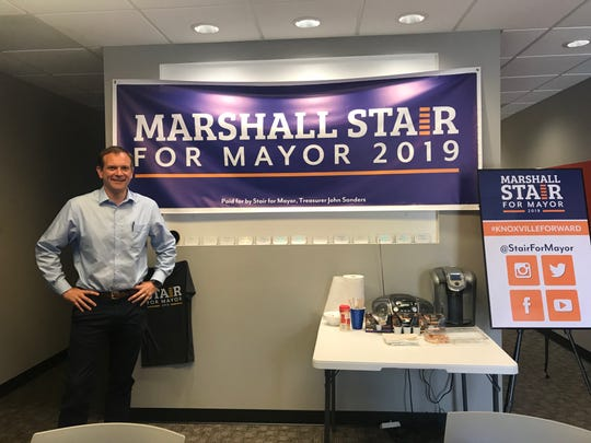 Councilman Marshall Stair stands at a big sign that greets visitors at the Knoxville mayoral campaign headquarters at CityScape.