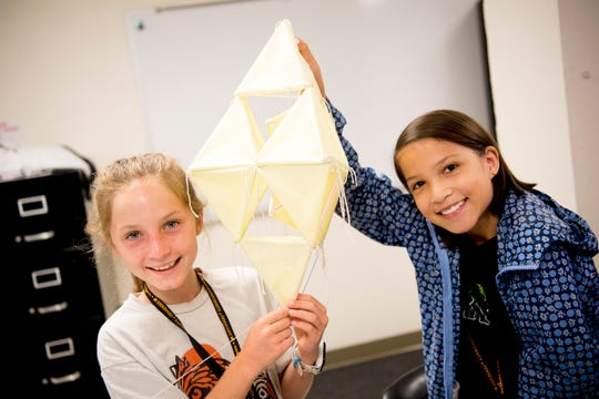 Clara Honeycutt and Allison Hodge hold up their kite during a STEM summer class at Greve Hall on the UTK campus in Knoxville, Tennessee on Wednesday, June 12, 2019. Students were building kites made of string, paper and straws to learn about aerodynamics.