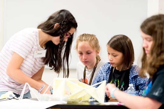 From left, Pellissippi State sophomore Hope Boucher, Clara Honeycutt, 10, and Allison Hodge, 10, put together a kite during a STEM summer class at Greve Hall on the UTK campus in Knoxville, Tennessee on Wednesday, June 12, 2019. Students were building kites made of string, paper and straws to learn about aerodynamics.