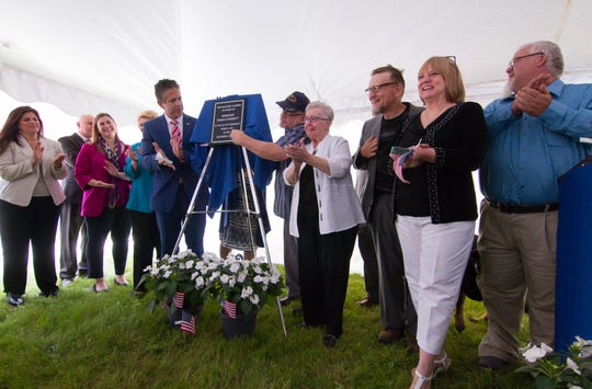 Members of the Burgett family, including Donald Burgett's wife Twyla (center), as well as several current and former state and federal politicians unveil a plaque commemorating Burgett for his service in the U.S. Army in World War II and renaming the Howell Post Office Friday, June 14, 2019.