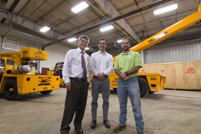 From left, Commercial Construction Inc. president and CEO Robert Garcia and sons Phillip and Gary pose in front of several cranes Thursday, June 13, 2019 in the Green Oak Township. facility.
