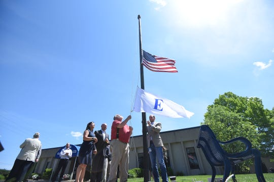A flag commemorating the Presidential Award for Exports awarded to Warren Rupp, Inc. is raised outside the company during a ceremony on Friday morning.