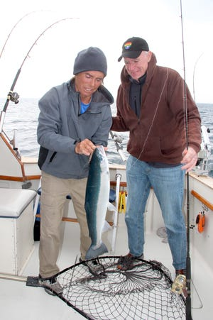 Charter captain Dan Fox unhooks a rainbow trout, or steelhead, caught by Milwaukee Mayor Tom Barrett during a fishing outing on Lake Michigan.