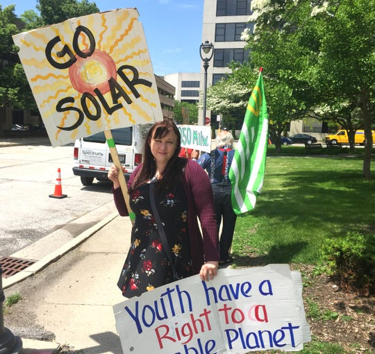 Amalisa Bodien of Milwaukee was among the people Friday who protested We Energies' proposed surcharge on residential and small business customers who have solar panels.