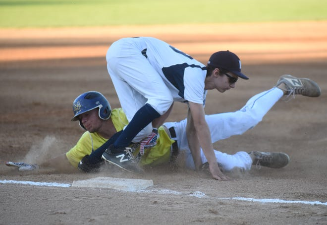 Lockeroom's Asa Smith dives into third base past Manchester's Logan Shepard on Thursday night.