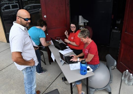 Baxter County Collector Teresa Smith (far right) and Chief Deputy Yvette Sigafus (second from right) help two Baxter County taxpayers with their paperwork Friday afternoon on the sidewalk in front of the former Flies International Pub & Grill building.