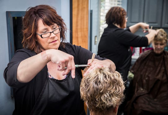 Mandy Toliver works with a client at Tangles salon in Muncie. Toliver took over management of the business after founder Nancy Finan died of cancer.