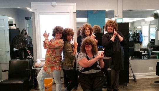 From left to right: Dionne Goeman, Lacey Bryan Burkett, Nancy Finan (front), Mandy Toliver and Amanda Coffey Gray pose for a picture at Tangles salon.