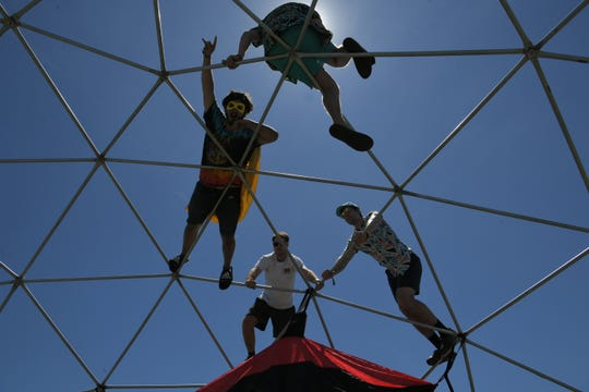 People on the frame of a dome in the group campground on Friday, June 14, during the Bonnaroo Music and Arts Festival in Manchester, Tenn.