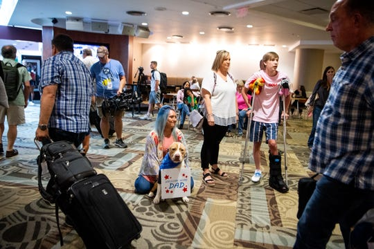 Haley Jones, Dana and Reese Self, from left, wait to introduce Franky to Retired Sgt. Major Chris Self at Nashville International Airport Friday, June 14, 2019, in Nashville, Tenn. Franky had his ears amputated after suffering from abuse and when Self heard his story he knew he wanted to adopt him. Self lost his leg in combat and returned from Afghanistan as civilian consultant.