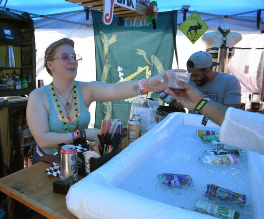 Kellie Copsey hands out beer made for Bonnaroo by Pontoon Brewing in the group campground on Friday, June 14, during the Bonnaroo Music and Arts Festival in Manchester, Tenn.