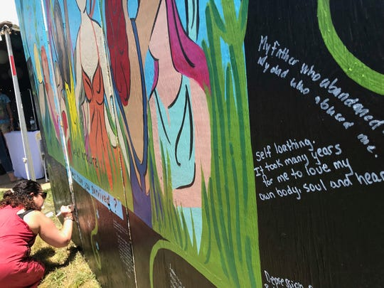 "A Bonnaroo attendee signs a mural created by Ruth Park in Camp SheRoo, which is the first women-only camping area offered at Bonnaroo Music and Arts Festival. The mural asks, ""What have you survived?"""