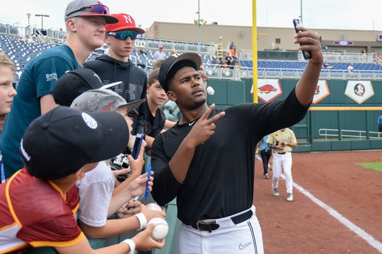 Vanderbilt Commodores starting pitcher Kumar Rocker (80) takes a selfie with fans during practice day before the start of the College World Series at TD Ameritrade Park Omaha on June 14, 2019.