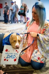 Haley Jones waits to introduce Franky to Retired Sgt. Major Chris Self at Nashville International Airport Friday, June 14, 2019, in Nashville, Tenn. Franky had his ears amputated after suffering from abuse and when Self heard his story he knew he wanted to adopt him. Self lost his leg in combat and returned from Afghanistan as civilian consultant.
