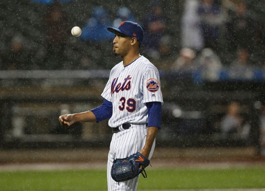 New York Mets relief pitcher Edwin Diaz tosses the ball while waiting out a rain delay as groundskeepers prepped the field during the ninth inning of the team's baseball game against the St. Louis Cardinals on Thursday, June 13, 2019, in New York. (AP Photo/Kathy Willens)