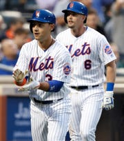 New York Mets' Michael Conforto, left, applauds as he and Jeff McNeil return to the dugout after Conforto hit a third-inning, two-run home against the St. Louis Cardinals in a baseball game Thursday, June 13, 2019, in New York. McNeil scored on the homer. (AP Photo/Kathy Willens)