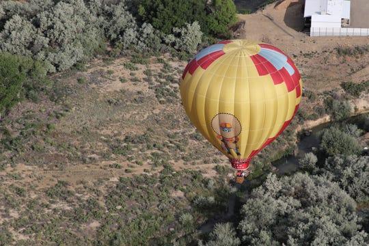 A hot air balloon flies near above the San Juan River, Friday, June 14, 2019, west of Bloomfield.