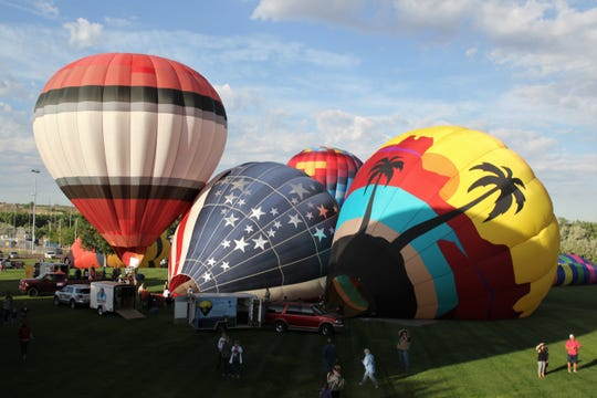 Volunteers, crews and pilots inflate hot air balloons, Friday, June 14, 2019, at the start of the San Juan River Balloon Rally in Bloomfield.