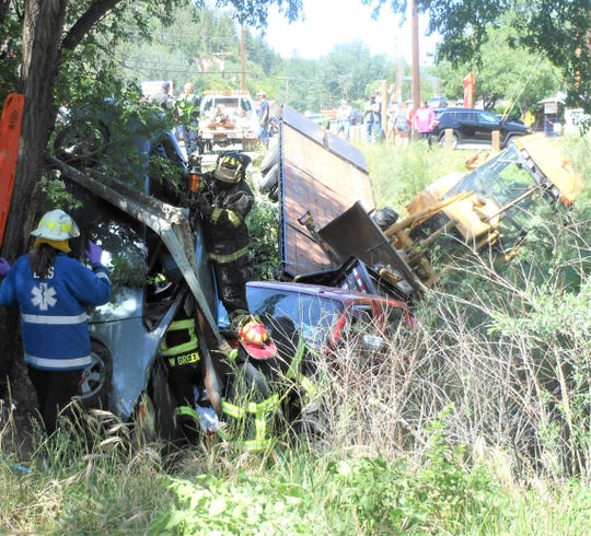 Ruidoso firemen work to free the driver of a vehicle that crashed over an embankment on Sudderth Drive at Two Rivers Park Thursday.