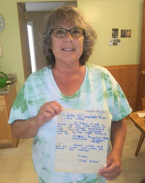 Canton resident Tina (Green) Allera holds the letter she placed in a bottle in 1974. It was found four years ago in three feet of sand near Traverse City.