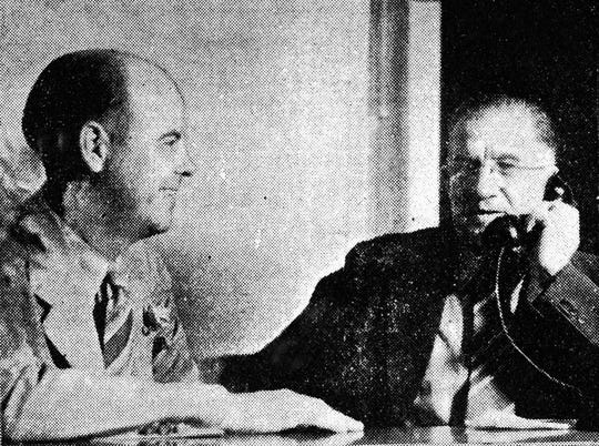 Opelousas Mayor David Hollier (right) placed the first long distance call using the new dial telephone system in Opelousas in 1940, as the manager of Southern Bell looks on.