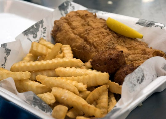 The fresh catch with fries and hushpuppies from the menu at the Olde East Hill Grill is ready to be served on Friday, June 14, 2019.