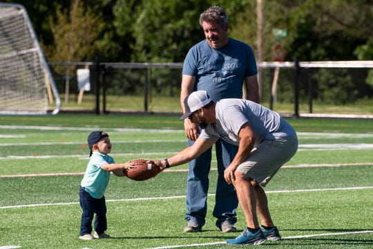 Littlestown youth football head coach Jason Shirdon hands off a football to 14-month-old Lincoln Herrington as Herrington's grandfather, Tim Kelley, watches during an open house at Thunderbolt Stadium on Friday, June 14, 2019.