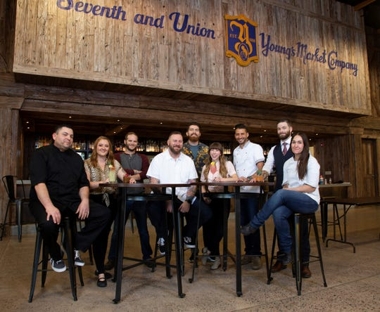 """The chefs and mixologists selected to take part in the Taste America Phoenix """"Raising the Bar"""" reception pose together at Young's Market in Phoenix."""