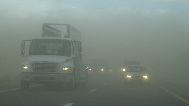 Cars drive north through a dust storm along I-10.