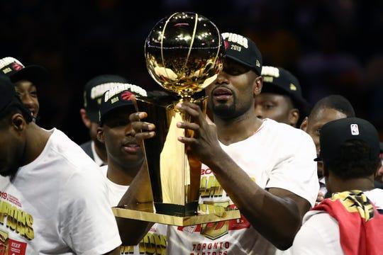 Serge Ibaka, jugador de El Congo, alza el trofeo de campeón por los Raptors.