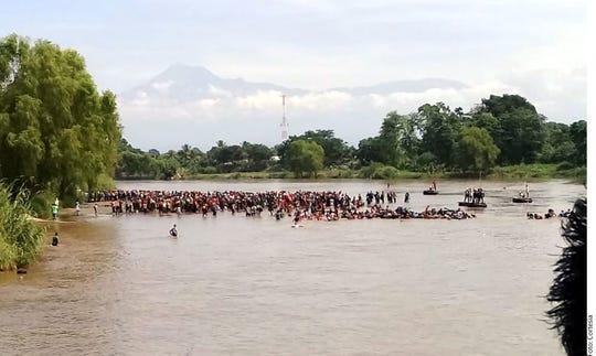Migrantes centroamericanos cruzan el río Suchiate hacia México.