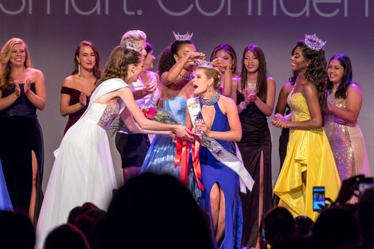 Lauren Molella, center, is shown being crowned Miss New York 2019 by her predecessor, Rahmeka Cox. She's being presented with a bouquet of flowers  by Miss New York's Outstanding Teen 2019 Sarah Lawrence. Miss America Nia Imani Franklin is in the yellow dress.  The pageant was held June 8 at the Paramount Hudson Valley Theater in Peekskill.