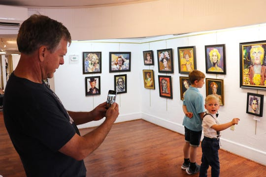 Warren Tracy Davis takes a photo of his grandchildren, Luke and Liam, who are observing Davis' art on June 12. Liam wants to be an artist like his grandfather when he grows up, Davis said.