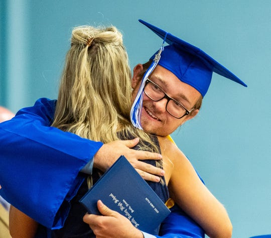 Jesse Euler receives a hug from Principal Kathy Bomba-Edgerton after accepting his diploma.