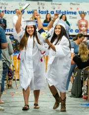 Esmeralda Castaneda (left) and Paulina Covian celebrate as they walk during the recessional.