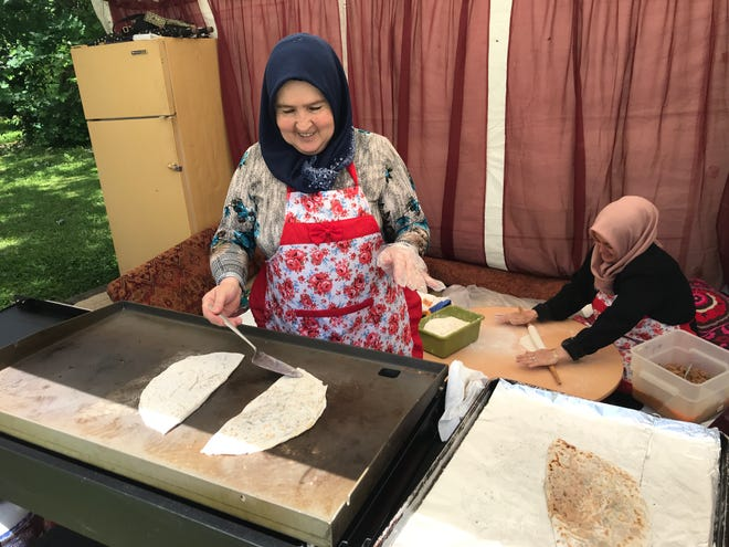 Ayse Celik cooks gozleme as Nazli Toklai rolls the dough at a booth at the International Food Festival on June 14, 2019.