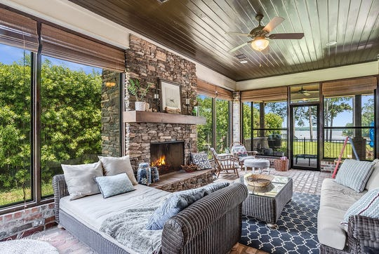 Cozy up in the four seasons enclosed sunroom with brick flooring and stone fireplace.