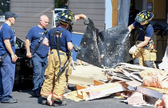 Firefighters dump debris off of a salon mat that was damaged when a motorist crashed into Salon Artist Suites on Friday, June 14, on Racket Drive in Sioux Falls.