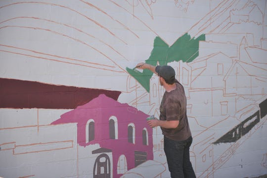 Chris DeBoer, who is directing the project with Amber Hansen, paints the pages of a book on the Hartford community mural.