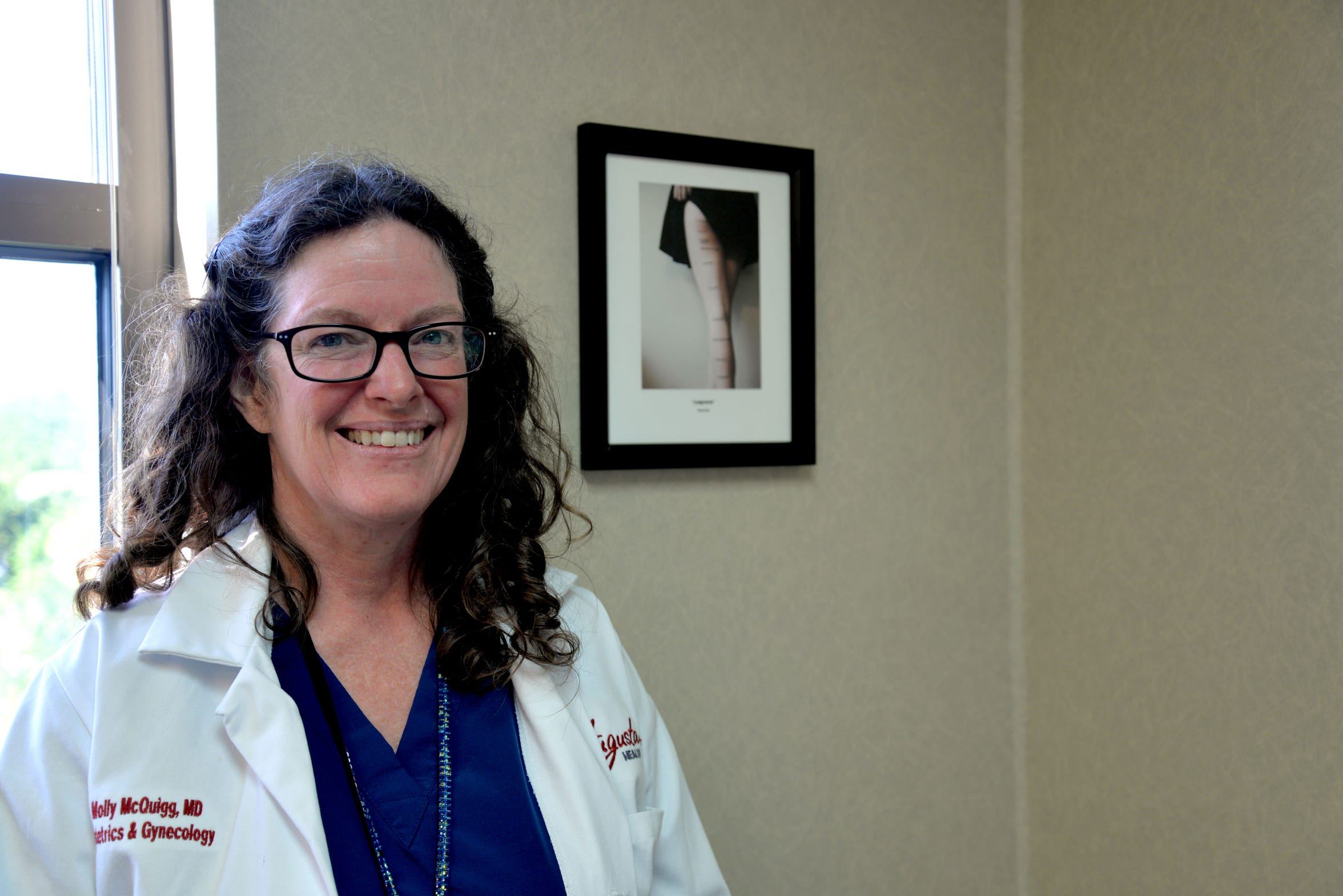 """Dr. Molly McQuigg at her office at Augusta Health Care for Women in Fishersville on June 13, 2019. She stands near one of her favorite prints """"Judgements"""" by Rosea Lake."""
