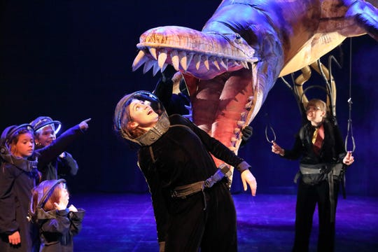 An explorer looks on in wonder as a marine dinosaur swims overhead in Erth's Prehistoric Aquarium Adventure.