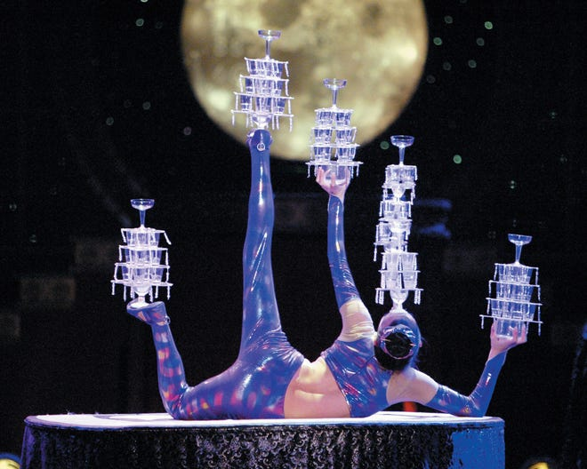 A contortionist with the Golden Dragon Acrobats balances champagne coupes on various appendages.