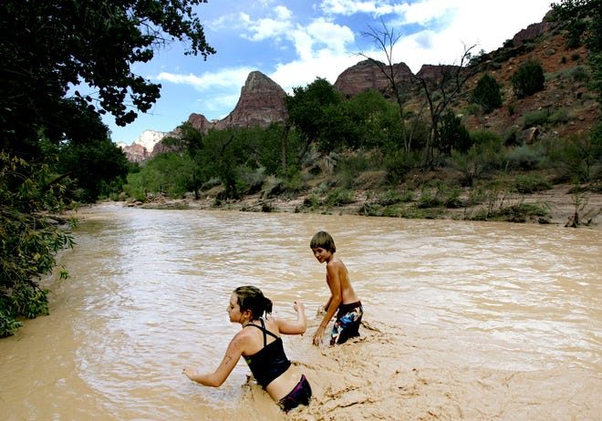 Visitors to Zion National Park traverse the Virgin River's unusually high water in this undated Spectrum file photo.