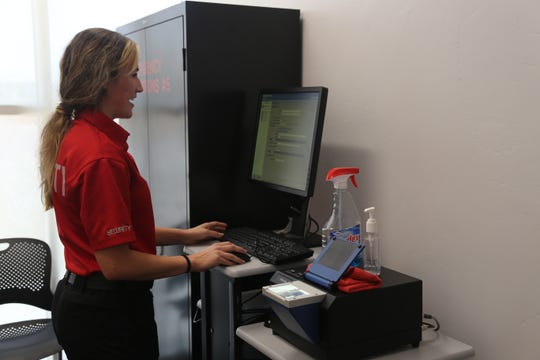 Mikaela Vega, with Dixie State University's Campus Police Department, demonstrates how to use the digital fingerprinting machine.